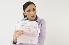 Woman Holding Bills. Portrait of a angry business woman holding loan documents isolated over white background Royalty Free Stock Photos