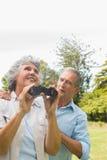 Woman holding binoculars with partner Stock Photo