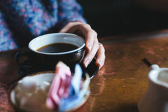 Woman Holding Black Ceramig Mug Filled With Black Coffee on Wooden Table Stock Photo