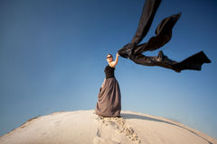 Woman holding black cloth on sand dune at windy day Stock Image