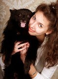 Woman holding black dog Royalty Free Stock Images