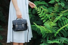 Woman Holding Black Leather Bag And Standing Beside Green Plant royalty free stock photos
