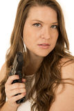 Woman holding a black pistol looking at the camera Stock Photography