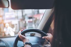 Woman holding on black steering wheel while driving a car. With traffic background Stock Photos