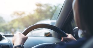 Woman holding on black steering wheel while driving a car. With traffic background Stock Image