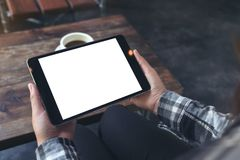 A woman holding black tablet pc with white blank screen with coffee cup on table background. Mockup image of a woman holding black tablet pc with white blank Stock Photos