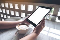 A woman holding black tablet pc with white blank screen with coffee cup on table background. Mockup image of a woman holding black tablet pc with white blank Stock Images