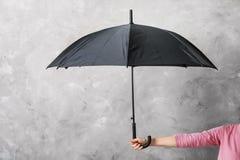 Woman holding black umbrella. On grey background Stock Photos