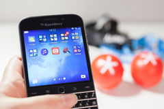 Woman holding a BlackBerry Classic. Moscow, Russia - February 1, 2015: Woman holding a BlackBerry Classic displaying icons on the screen, against a BlackBerry Stock Photos