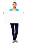 Woman Holding Blank Billboard. Full length portrait of happy young woman holding blank billboard over white background. Vertical shot Royalty Free Stock Images