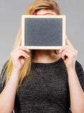 Woman holding blank black board on face Stock Photo