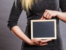 Woman holding blank black board on stomach Stock Photo