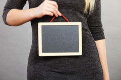 Woman holding blank black board on stomach. Tummy belly problems, pain, digestion, constipation concept. Woman holding blank black board on stomach Stock Photo