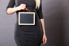Woman holding blank black board on stomach. Tummy belly problems, pain, digestion, constipation concept. Woman holding blank black board on stomach Stock Photography