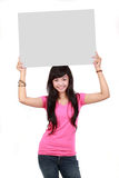 Woman holding a blank board. Portrait of a cute young woman holding a blank board isolated over white background Royalty Free Stock Photos