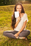 Woman holding blank board outdoors. Closeup of young beautiful woman with long dark hair, holding blank white board on green background of summer nature Royalty Free Stock Photos