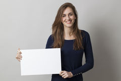 Woman holding blank board or paper for an advert Royalty Free Stock Photo