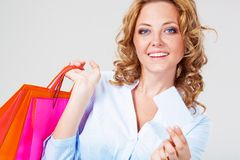 Woman holding blank card and bags Royalty Free Stock Images