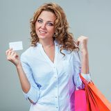 Woman holding blank card and bags Stock Images