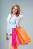 Woman holding blank card and bags Stock Photography