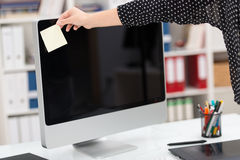 Woman holding a blank card in front of a monitor. Woman holding a blank business card in front of a desktop computer monitor with a blank screen facing the Royalty Free Stock Photography