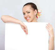 Woman holding a blank paper. Beautiful woman holding a blank paper, billboard Stock Image