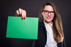 Woman holding blank paper with copyspace. Isolated on dark background stock image