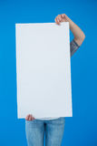 Woman holding a blank placard in front of her face Royalty Free Stock Image