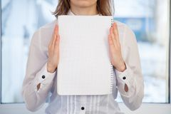 Woman holding blank ring-bound notebook Stock Photo