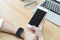 Woman holding a blank screen phone and a laptop and put a smart watch, film effect. royalty free stock photo