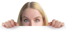 Woman Holding Blank Sheet of Paper. A blond woman is holding a blank sheet of paper to the camera. You can only see her eyes. She is on an isolated background Royalty Free Stock Photo