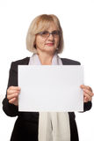 Woman holding blank sheet of paper. Smart woman with blond hair and spectacles holding a blank sheet of white paper for added text on white background stock photography