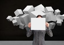 Woman holding blank sheet of paper in front of her face and white cubes in background Stock Photos