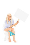 Woman holding a blank sign seated on a toilet Royalty Free Stock Photo