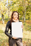 Woman holding a blank sign in woodland Stock Photography