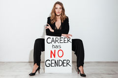Woman holding blank with text about career gender. Royalty Free Stock Photo