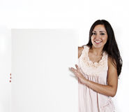 Woman holding a blank white sign. A smiling young woman holding a blank white sign Royalty Free Stock Photo