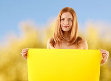 Woman holding blank yellow banner over nature. Background Stock Image