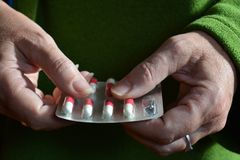 Woman holding a blister pack of red & white capsules royalty free stock photo