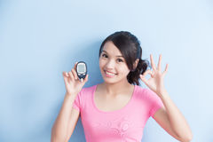 Woman holding blood glucose meter. Woman holding a blood glucose meter to prevention diabetes isolated on blue background, asian stock photos