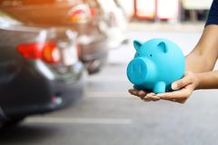 Woman holding blue piggy bank with standing near the car for save money to buy vehicle & insurance.  royalty free stock photography