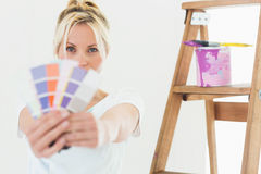 Woman holding blurred color swatches in new house Royalty Free Stock Photography