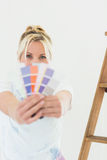 Woman holding blurred color swatches in new house Stock Image