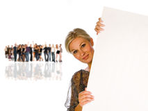 Woman holding a board. The picture shows pretty woman holding a blank over white board and a crowd in the background Stock Photos