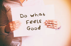 Woman holding board with the phrase do what feels good written on it. retro filtered image Royalty Free Stock Photography