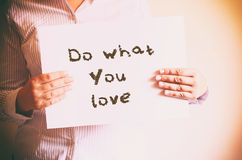 Woman holding board with the phrase do what you love written on it. retro filtered image Royalty Free Stock Photography
