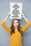 Woman holding board with text and winking. Portrait of a cheerful woman holding board with text: do more of what makes you happy and winking on gray background Royalty Free Stock Images