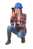 Woman holding bolt cutter. Whilst in crouching position Royalty Free Stock Photos