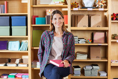 Woman Holding Book Against Shelves In Shop Stock Photo