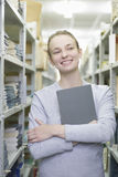 Woman Holding Book In Library Aisle Stock Photo